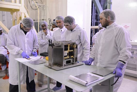 Figure 1: (Left to right, foreground) Mission Manager Grant Bonin, Propulsion Engineer Ben Risi, and Systems Engineer Scott Armitage preparing for launch vehicle integration